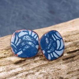 Copper enamel ear studs with a blue and indigo decorative abstract floral patterning. The curvy square shape is about 16mm and a sterling silver ear post with scroll have been soldered onto the back. The coloured enamel powder is sifted onto the metal before being fused at high temperature in a kiln. The additional patterning is then added and sealed on top. Due to the nature of this process each item is truly unique and individual. All of my cherry pie jewellery is gift wrapped for you in a cotton linen hand stamped gift pouch. All orders include Free UK Postage and Packing.