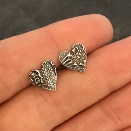 Silver heart stud earrings with floral pattern
