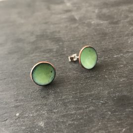 Handmade copper enamel stud earrings in a beautiful fresh celadon green colour. The earrings are 13mm in size and have a sterling silver post and scroll on back.