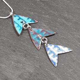 Copper enamel patterned 3 part pendant of triangle ' whale tail' shapes. Colourful pendant with contrasting pattern of enamel.