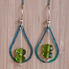 Green pantina brass teardrop and czezh glass earrings hung on a wooden stand