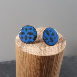 Geometric patterning of two shades of blue on these 18mm copper enamel stud earrings. They have been kiln fired to create a unique surface design and have been finished with a sterling silver ear post and scroll.