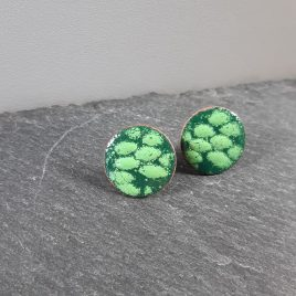 Beautiful tones of dark green and fresh grass green enamel are layered together to create a natural pattern on these copper stud earrings. The ear studs are 18mm in diameter and have been finished with a sterling silver post and scroll back. All MyCherryPie Jewellery includes a bespoke 100% recyclable gift box.