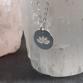 Beautiful solid sterling silver round charm with a lotus flower cut out. Contemporary necklace that works well on its own as well as layered with other charm necklaces of differing lengths. The Lotus flower is regarded in many different cultures, especially in eastern religions, as a symbol of purity, enlightenment, self-regeneration and rebirth. Its characteristics are a perfect analogy for the human condition: even when its roots are in the dirtiest waters, the Lotus produces the most beautiful flower.