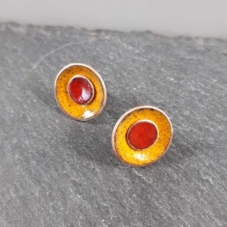 Colourful and Creative Duo Enamel Stud Earrings. These earrings combine two different colours of kiln fired enamel, in this case a warm sunflower yellow on the outside and bright burnt orange/red on the inside. The earrings can be separated so that the smaller middle colour can be worn separately. The enamel colours are fired on to a copper base and have a sterling silver post and scroll attached to the back. The size of the larger disk is 18mm and the smaller inner one is 8mm. A great gift for any colour lover or aurasoma enthusiast.