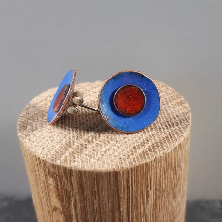 Colourful and Creative Duo Enamel Stud Earrings. These earrings combine two different colours of kiln fired enamel, in this case a cool ultramarine blue on the outside and bright burnt orange/red on the inside. The earrings can be separated so that the smaller middle colour can be worn separately. The enamel colours are fired on to a copper base and have a sterling silver post and scroll attached to the back. The size of the larger disk is 18mm and the smaller inner one is 8mm. A great gift for any colour lover or aurasoma enthusiast.