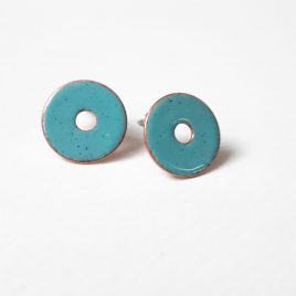 Unusual and eye catching earrings for summer and everyday wear. Round copper ear studs enamelled in a cool seablue colour. With an all important hole in the middle. These earrings are 14mm in size and have a sterling silver ear post and scroll on the back. Other colours are available on request.