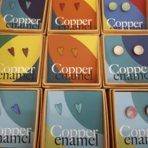 Circular and heart shaped earrings on colourful backing cards sitting in boxes