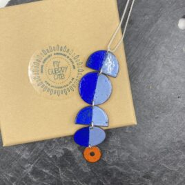 Statement circle necklace with blue tones and contrasting orange colour.
