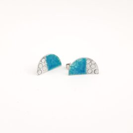 Half Moon Sterling Silver and Aquamarine Enamel Stud Earrings. Beautiful combination of stamped sterling silver and transparent aquamarine enamel make these earrings stand out. The delicate stamped circle pattern creates a texture under the enamel. These stud earrings are 17 x 9mm and the ear post is towards the top of the half moon shape allowing them to hang in a crescent shape from the ear.